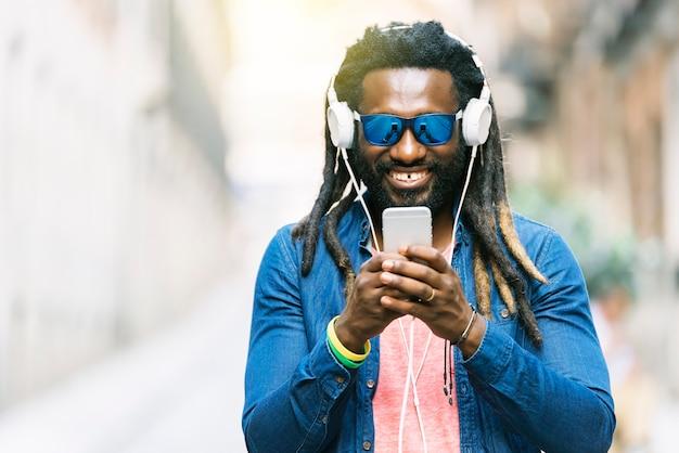 Retrato ao ar livre de jovem africano bonito, escrevendo mensagem e ouvindo música.
