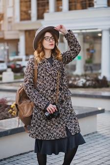 Retrato ao ar livre de jovem elegante com mochila marrom, vestindo casaco e chapéu. mulher atraente com cabelo encaracolado, falando ao telefone enquanto toma café na rua e espera os amigos