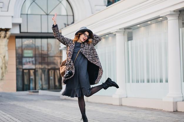 Retrato ao ar livre de jovem elegante com mochila marrom, vestindo casaco e chapéu. mulher atraente com cabelo encaracolado falando, pulando e se divertindo.