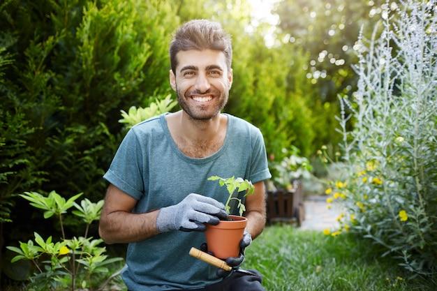 Retrato ao ar livre de jovem homem barbudo bonito caucasiano em camisa azul e luvas, sorrindo na câmera, segurando o pote com flores nas mãos, trabalhando no jardim.