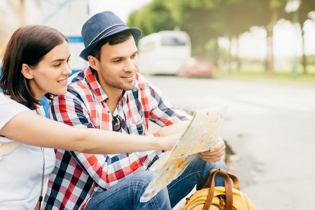 Retrato ao ar livre de jovem homem e mulher sentados juntos no banco, descansando por um minuto após uma longa viagem pela cidade grande, olhando no mapa, apontando ou indicando o local onde não estiveram