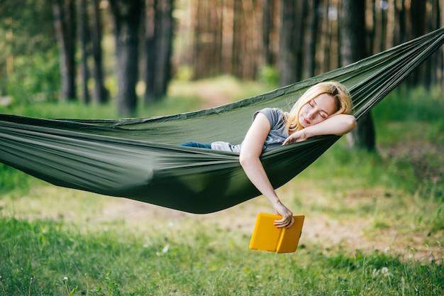 Retrato ao ar livre de jovem loira linda dormindo na rede na floresta de verão ensolarado com e-book na mão.