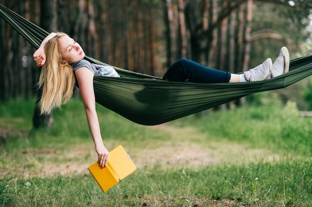 Retrato ao ar livre de jovem loira linda dormindo na rede na floresta. e segurando o e-book na mão.