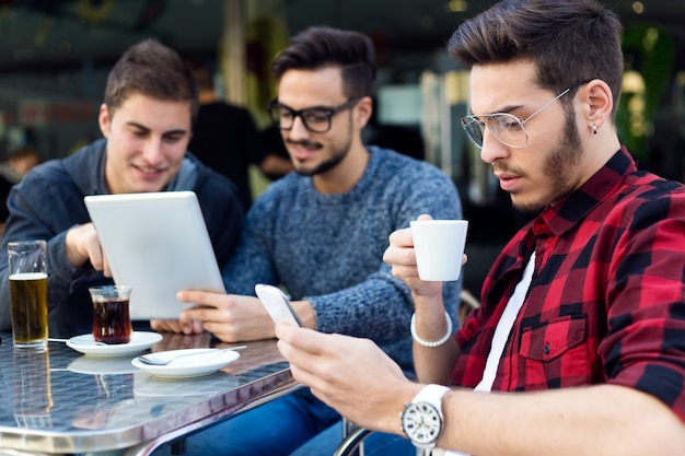 Retrato ao ar livre de jovens empresários que trabalham no café bar.