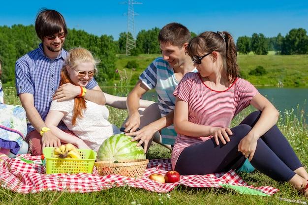 Retrato ao ar livre de jovens fazendo um piquenique, comer melancia
