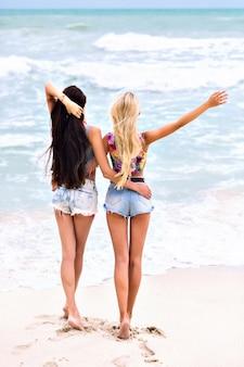 Retrato ao ar livre de menina bonita com cabelo castanho escuro, posando com os olhos fechados, desfocar o fundo do mar. jovem loira atraente com tatuagem de braço se divertindo com o amigo durante as férias de verão.