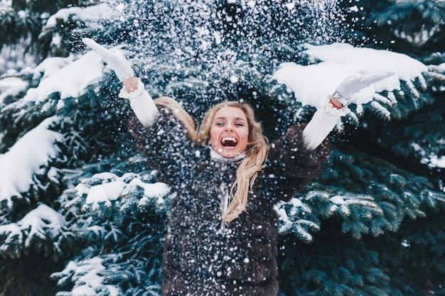 Retrato ao ar livre de menina de natal, mulher bonita, soprando neve na floresta de inverno