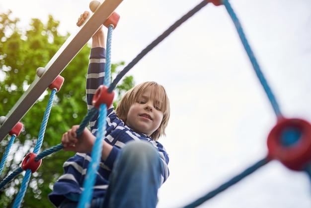 Retrato ao ar livre de menino pré-escolar bonito subir no parque infantil