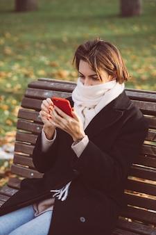 Retrato ao ar livre de mulher caucasiana, vestindo um casaco de inverno preto e lenço, sentado no banco no parque com telefone celular.