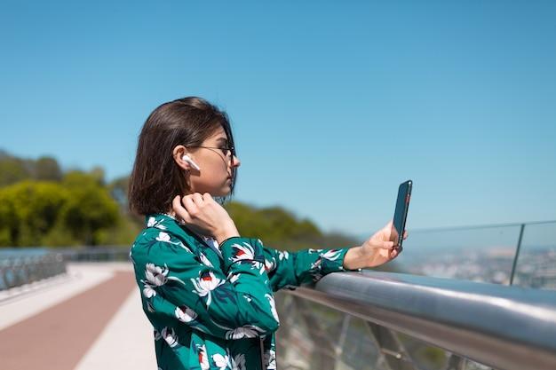 Retrato ao ar livre de mulher com camisa verde casual em dia de sol fica na ponte, olhando na tela do telefone, fones de ouvido bluetooth sem fio