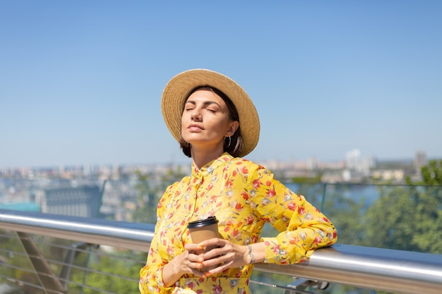 Retrato ao ar livre de mulher com vestido amarelo de verão e chapéu com uma xícara de café, aproveitando o sol, fica na ponte com uma vista incrível da cidade