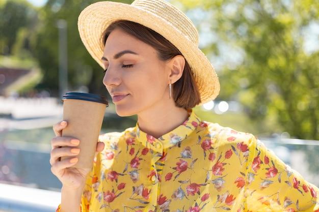 Retrato ao ar livre de mulher com vestido amarelo de verão e chapéu com uma xícara de café, aproveitando o sol