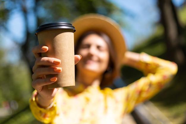 Retrato ao ar livre de mulher com vestido amarelo de verão e chapéu com uma xícara de café no parque