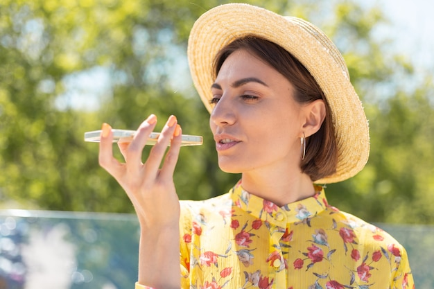 Retrato ao ar livre de mulher com vestido amarelo de verão e chapéu gravando mensagem de voz no telefone