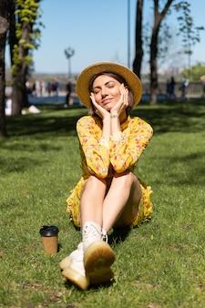 Retrato ao ar livre de mulher com vestido amarelo de verão e chapéu sentada na grama do parque