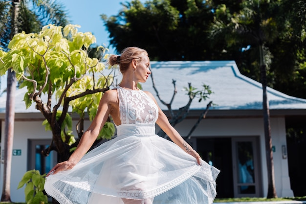 Retrato ao ar livre de mulher com vestido de noiva branco em villa em dia ensolarado, vista tropical