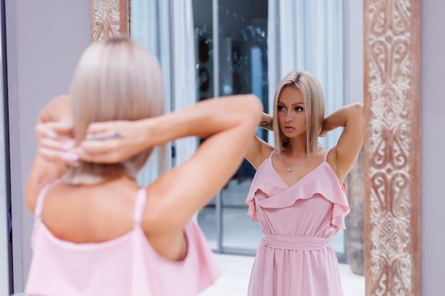 Retrato ao ar livre de mulher com vestido rosa romântico usando colar