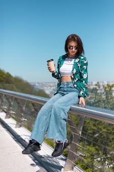 Retrato ao ar livre de mulher de camisa verde com uma xícara de café, aproveitando o sol, fica na ponte com uma vista incrível da cidade pela manhã