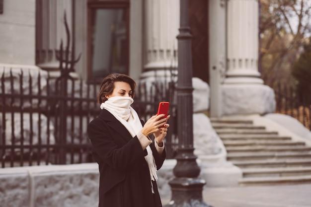 Retrato ao ar livre de mulher de casaco de inverno preto e lenço branco no meio do rua, segurando o telefone móvel.