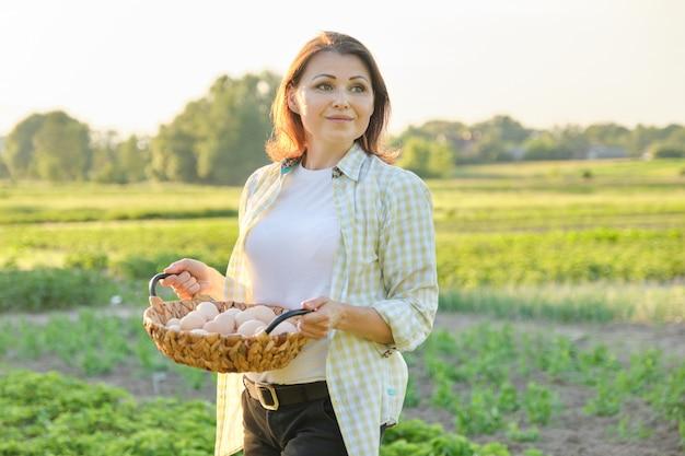 Retrato ao ar livre de mulher de fazendeiro com cesta de ovos de galinha fresca, fazenda