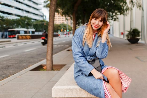 Retrato ao ar livre de mulher elegante muito feliz com casaco azul, sentada no banco na rua