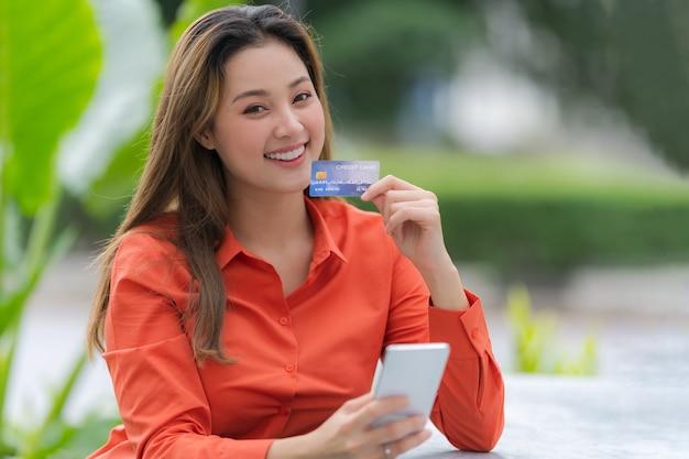 Retrato ao ar livre de mulher feliz segurando um telefone inteligente com cartão de crédito e um rosto sorridente no shopping