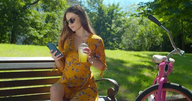 Retrato ao ar livre de mulher jovem e atraente em uma bicicleta usado smartphone e bebendo limonada em um banco do parque.