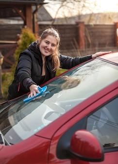 Retrato ao ar livre de mulher lavando o pára-brisa do carro