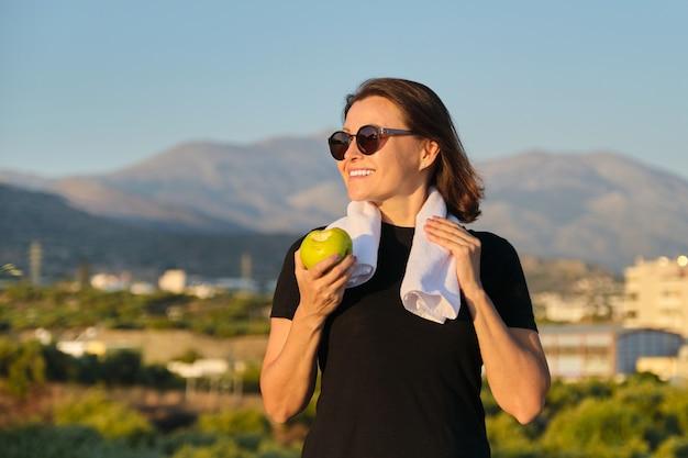Retrato ao ar livre de mulher madura desportiva com uma maçã