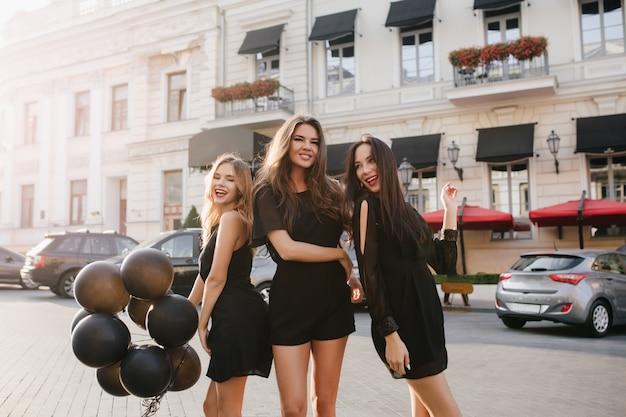 Retrato ao ar livre de mulheres magras se divertindo juntas depois da festa e andando pela rua