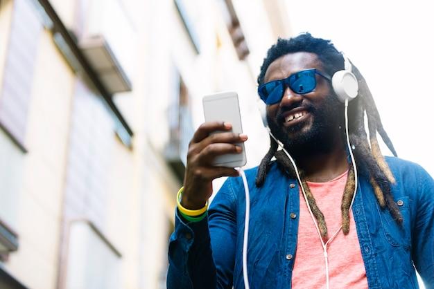 Retrato ao ar livre de música jovem africano bonito ouvindo.
