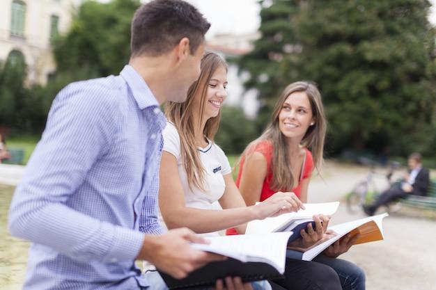Retrato ao ar livre de três estudantes sorridentes estudando em um parque