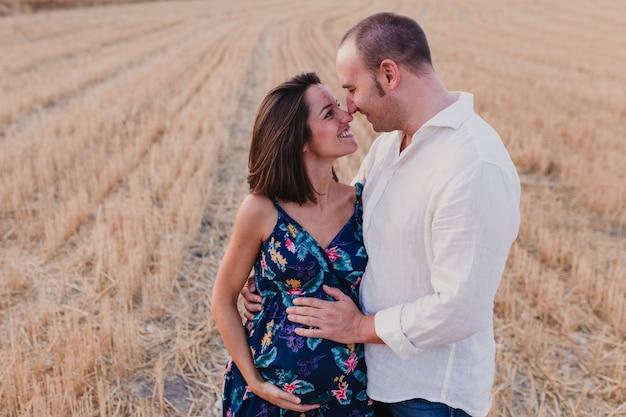 Retrato ao ar livre de um jovem casal grávida em um campo amarelo. estilo de vida familiar ao ar livre.