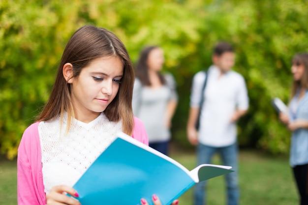 Retrato ao ar livre de um jovem estudante sorridente na frente de um grupo de estudantes