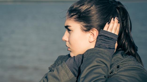 Retrato ao ar livre de uma adolescente pensativa