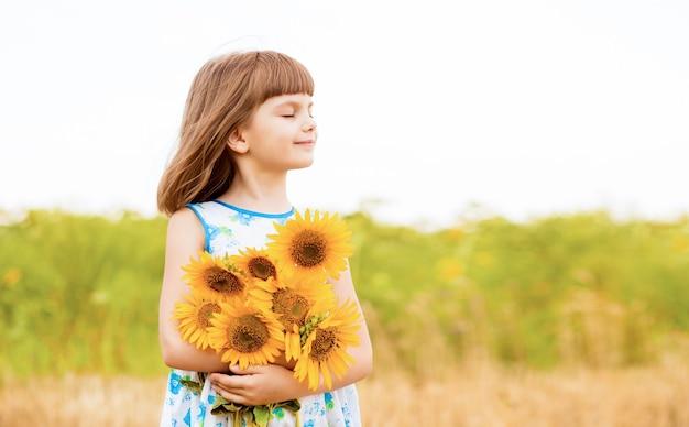 Retrato ao ar livre de uma adorável menina caminhando em um campo de girassóis colhendo e coletando buquê