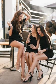 Retrato ao ar livre de uma atraente mulher bronzeada brincando com seus longos cabelos e segurando uma taça de champanhe com as amigas