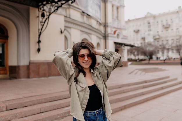 Retrato ao ar livre de uma atraente mulher de cabelos escuros, usando óculos escuros elegantes e jaqueta jeans, caminhando na cidade de primavera