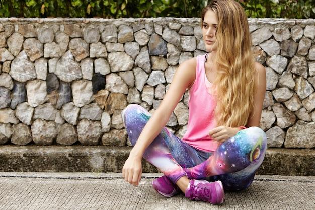 Retrato ao ar livre de uma bela atleta caucasiana com longos cabelos loiros, vestindo uma blusa esportiva rosa e leggings com estampa espacial, sentada e relaxando na calçada de pedra com as pernas cruzadas após uma longa corrida