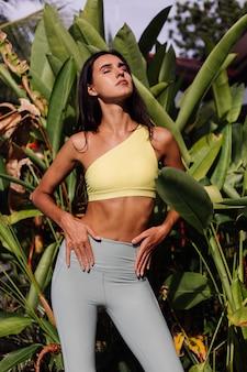 Retrato ao ar livre de uma bela mulher caucasiana, esguia, esportiva, bronzeada, com blusa amarela e leggings sobre plantas tropicais