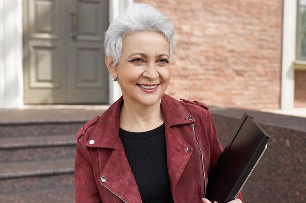 Retrato ao ar livre de uma funcionária de meia-idade, elegante e alegre, com cabelo curto e grisalho, posando do lado de fora de um edifício moderno com uma pasta