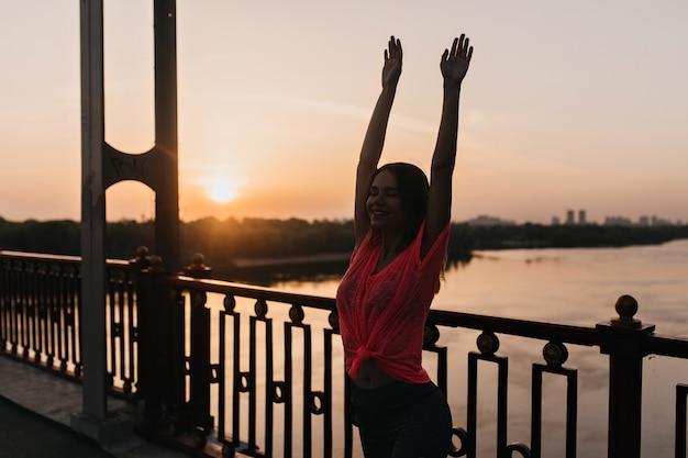 Retrato ao ar livre de uma garota cativante em t-shirt rosa, alongamento à noite. mulher caucasiana alegre fazendo ioga