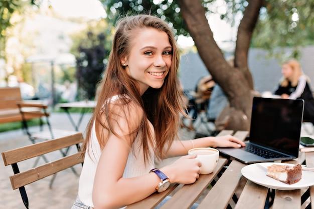 Retrato ao ar livre de uma garota feliz e sorridente com cabelo comprido e olhos grandes, trabalhando ao ar livre com um laptop