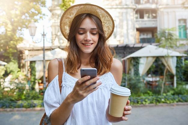 Retrato ao ar livre de uma jovem adorável e feliz usando um chapéu de verão elegante e um vestido branco, sentindo-se relaxado, usando o smartphone e bebendo café para viagem no parque