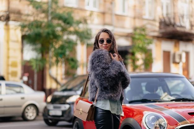Retrato ao ar livre de uma jovem atraente e elegante usando pele e óculos elegantes, andando na rua ensolarada da cidade