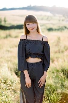 Retrato ao ar livre de uma jovem atraente em um elegante terno preto, curtindo a natureza, posando para a câmera em um lindo campo verde de verão em um dia ensolarado