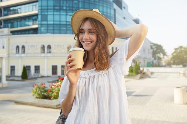 Retrato ao ar livre de uma jovem atraente sorridente, usando um elegante chapéu de verão e um vestido branco, se sentindo feliz, caminhando pela cidade e bebendo café para viagem