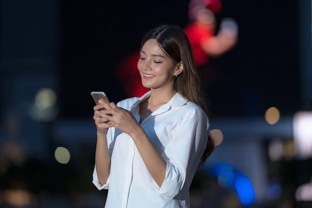 Retrato ao ar livre de uma jovem com uma carinha sorridente, usando um telefone, que caminha por uma cidade à noite