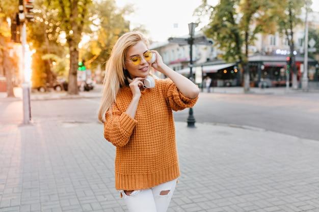 Retrato ao ar livre de uma jovem elegante com um suéter de lã ouvindo música com os olhos fechados e sorrindo
