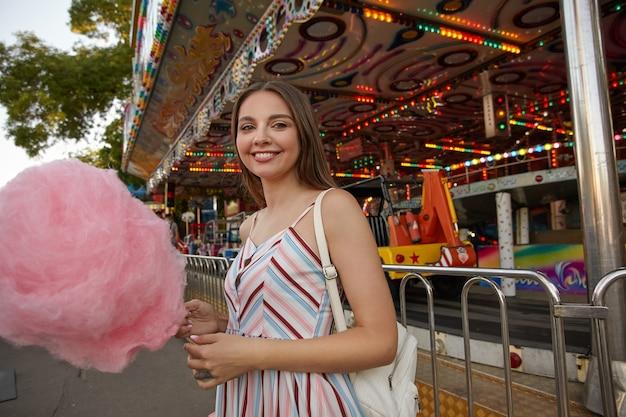Retrato ao ar livre de uma jovem encantadora em um vestido leve com alças em pé sobre um parque de diversões em um dia quente de verão, segurando um algodão doce na mão e olhando com um largo sorriso